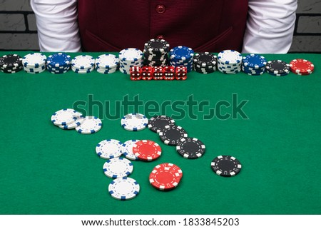 different bets and chips on the green poker table in front of the dealer