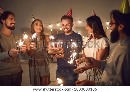 Group of cheerful young people in cone party hats with lit sparklers in hands wishing happy birthday to their friend whos about to blow candles on his birthday cake during celebration at home Royalty-Free Stock Photo #1833880186