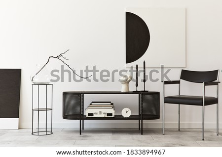 Interior design of modern living room with black stylish commode, chair, mock up art paintings, lamp, book, candlestick, decorations and elegant accessories in home decor. Template. Royalty-Free Stock Photo #1833894967