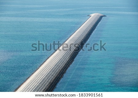 Breakwater made of concrete blocks. Modern wave protection construction for harbor safety Royalty-Free Stock Photo #1833901561