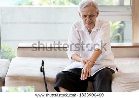 Old elderly patient suffer from gout,rheumatoid,chronic arthritis with severe pain,injury wrist bones,Asian senior woman is rubbing and massaging her wrist,beriberi in hands or numbness of the fingers