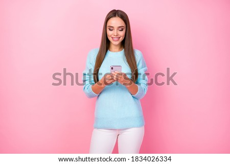 Photo of attractive lady hold telephone hands enjoy communication friends boyfriend wear knitted blue sweater white trousers isolated pastel pink color background
