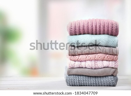 Stack of knitted textured clothing on table empty space.Colorful winter clothes,warm apparel.Heap of knitwear.Autumn garment. Royalty-Free Stock Photo #1834047709