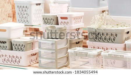 Organization of home space, storage and coziness, a lot of plastic household goods, new clean container boxes with a lid for easy storage of things Royalty-Free Stock Photo #1834055494