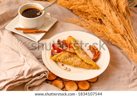 gluten-free keto crepes with peach and almonds and sweet berries. a cup of coffee with cinnamon. selective focus. autumn healthy breakfast or dessert concept. #1834107544