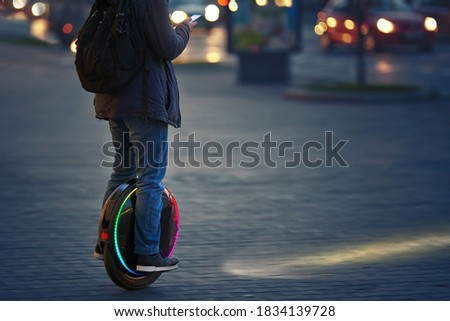 Man riding fast on electric unicycle on city street at night with diode headlights. Mobile portable individual transportation vehicle. Night riding, man on electric mono-wheel riding fast (EUC) #1834139728