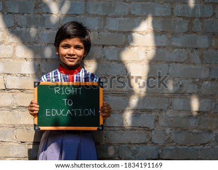 """A little Indian Rural Girl holding a Green Board written """" Right To Education"""", A Concept Image.    Royalty-Free Stock Photo #1834191169"""