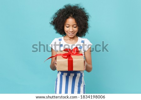 Excited little african american kid girl 12-13 years old in striped clothes isolated on blue background. International Women's Day birthday, holiday concept. Hold red present box with gift ribbon bow Royalty-Free Stock Photo #1834198006