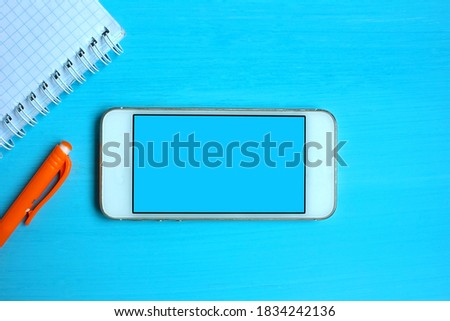 Smartphone blank blue screen, phone mockup. Template for infographic or interface design. On the office table there is a mobile phone, a notebook and an orange pen.