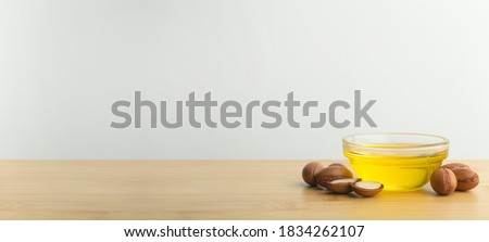 Argan oil banner background. Argan nuts  and oil on a wooden table on a empty white background. Copy space Royalty-Free Stock Photo #1834262107