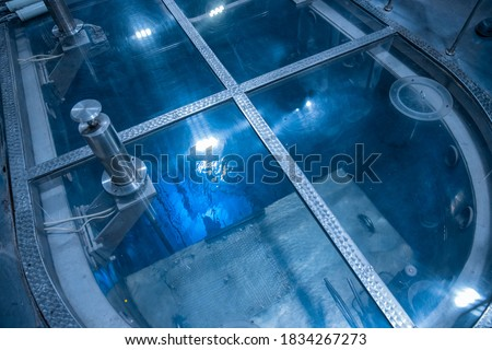 Blue glow water of nuclear reactor core powered, caused by Cherenkov radiation, fuel plates industrial uran. Royalty-Free Stock Photo #1834267273