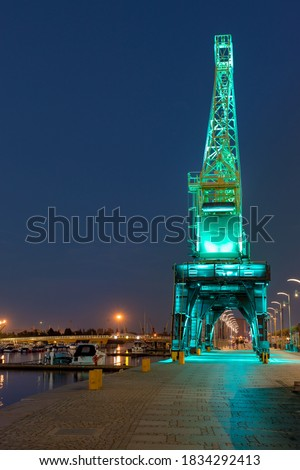 Szczecin. Illuminated cranes on the riverside city boulevards. Walking place for residents. View after dusk Royalty-Free Stock Photo #1834292413
