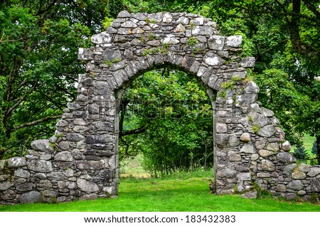 Old stone entrance wall in green landscaped garden #183432383