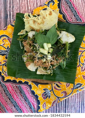 Pecel is Vegetables Salad from Indonesia. Pecel on banana leaf with peanut sauce, yellow batik. Selective focus picture