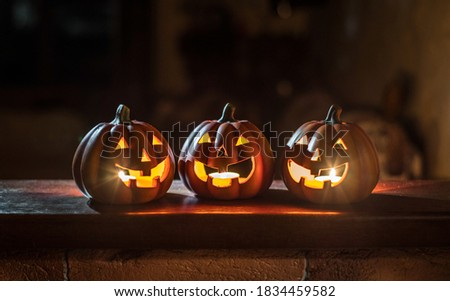 Three cheerful glowing Halloween pumpkins stand on a wooden table on a dark background.