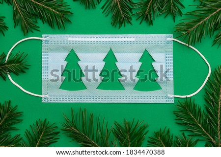 Medical protective mask with a cut-out silhouette of a Christmas tree on a green background.Frame of Christmas tree branches around the mask.Christmas and Happy New Year concept, coronavirus concept.