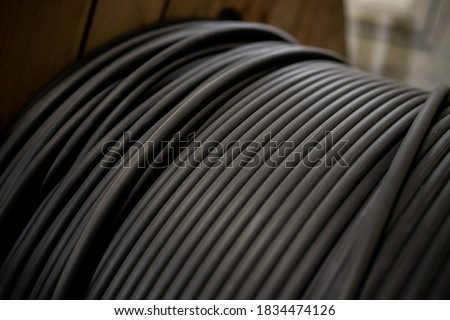 Vertical coils ndustrial wires. Many turns of main electrical cable is closeup. Roll of outdoor fiber optic signal shielded cables. Wooden Coils of powerful black telecommunications wire Royalty-Free Stock Photo #1834474126