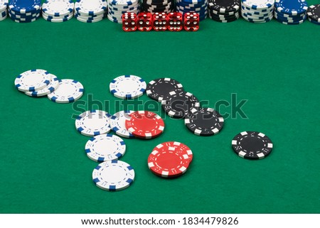 chips and dice are scattered on the green cloth of the poker table, background close-up