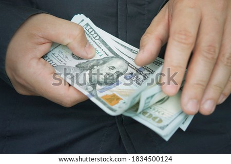 counting. money with hands. A male employee counts the salary in dollars, close-up. Cash for pocket expenses. Tips in 100 bills. #1834500124