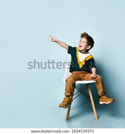 brunette kid in colorful t-shirt and brown pants. Smiling and pointing at something by forefinger, sitting on white chair against blue studio background. Childhood, fashion. Close up, copy space Royalty-Free Stock Photo #1834529371