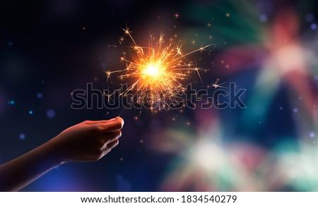 Hand holding a burning sparkler against fireworks background