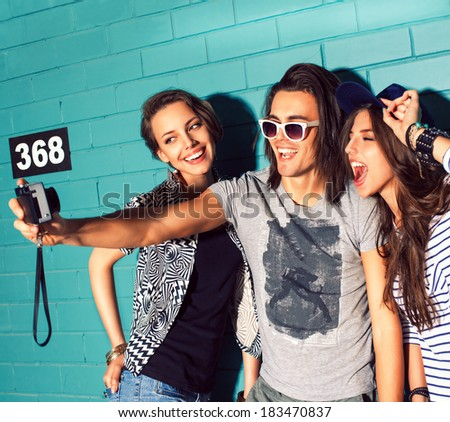 three young smiling people take picture of themselves in front of light blue brick wall