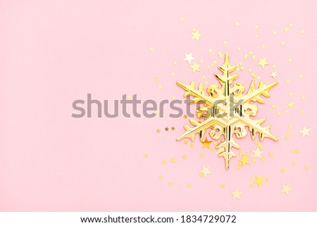 Pink christmas flatly. Golden snowflake and confetti at pastel pink background. New year layout with copyspace.