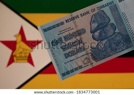 A unique one hundred trillion dollar banknote of the 2008 African State of Zimbabwe against the backdrop of the Zimbabwe flag