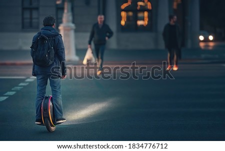 Man riding fast on electric unicycle through crosswalk at night with diode lights. Mobile portable individual transportation vehicle. Night riding, man on electric mono-wheel riding fast (EUC) #1834776712