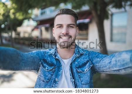 Portrait of young handsome man wearing casual clothes and taking a selfie outdoors in the street.