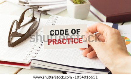 Closeup on businessman holding a card with CODE OF PRACTICE message, business concept image with soft focus background and vintage tone