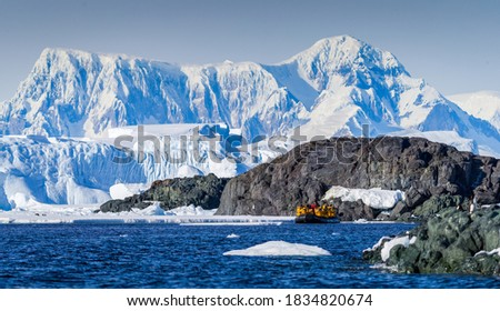 Expedition members traveling in a zodiac in Antartica  Royalty-Free Stock Photo #1834820674