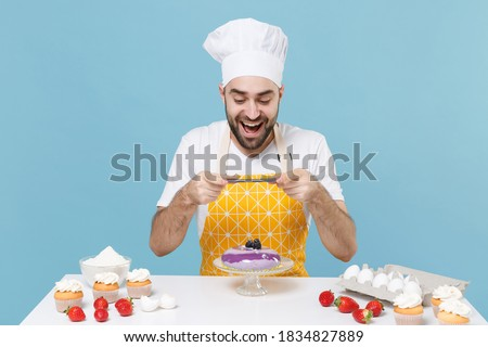 Excited young male chef or cook baker man in apron white t-shirt toque chefs hat cooking at table isolated on blue background. Cooking food concept. Taking pictures of dessert cake on mobile phone