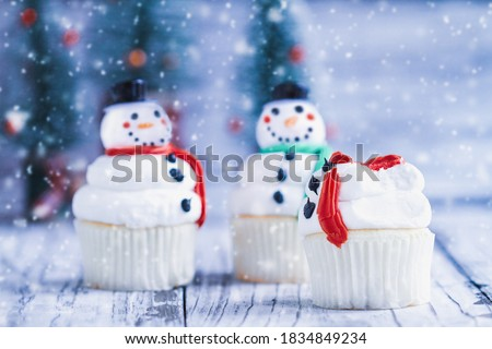 Iced Christmas Snowman cupcake with part bitten off or eaten. Other snowmen with carrot nose, Santa hat, and scarf. Selective focus with blurred background.