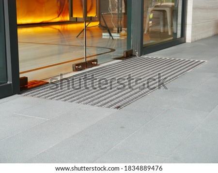 Entrance mat on the floor of main entrance of luxury condominium for preventing dust from shoes into building. It made of PP carpet and aluminium track which total size is 50 cm width and 1.6 m  Royalty-Free Stock Photo #1834889476