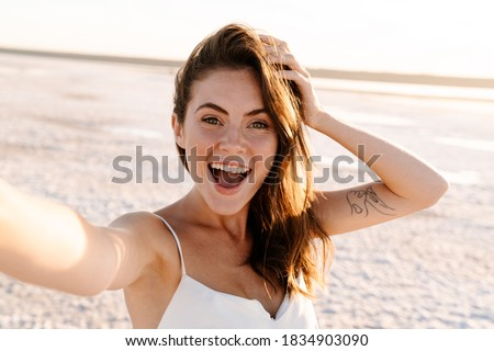 Picture of a cute surprised excited young pretty girl walking outdoors at the beach and taking a selfie by camera