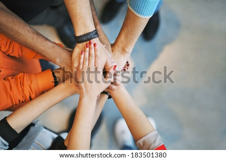 Multiethnic group of young people putting their hands on top of each other. Close up image of young students making a stack of hands. Royalty-Free Stock Photo #183501380