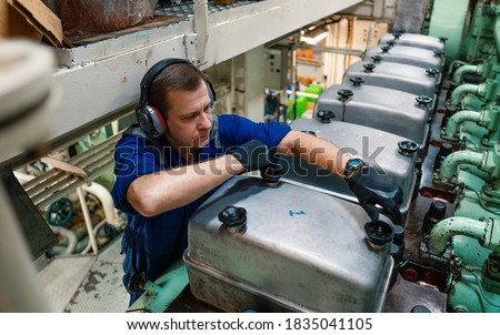 Marine engineer officer reparing vessel engines and propulsion in engine control room ECR. Ship onboard maintenance Royalty-Free Stock Photo #1835041105