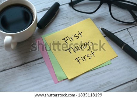 Selective focus of a cup of coffee, pen, glasses and memo notes written with First Things First on white wooden background. Royalty-Free Stock Photo #1835118199
