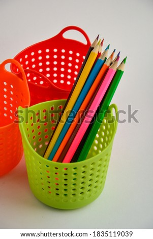 Colored sharpened pencils for drawing in a green pencil holder close-up on a light background