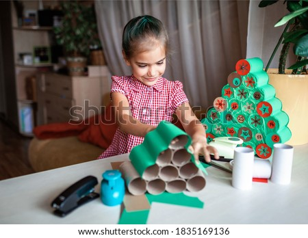 Cute little kids making handmade advent calendar with toilet paper rolls at home. Glue, colored paper, cut punch to hide sweets and candies in rolls. Seasonal activity for kids, zero waste holidays #1835169136