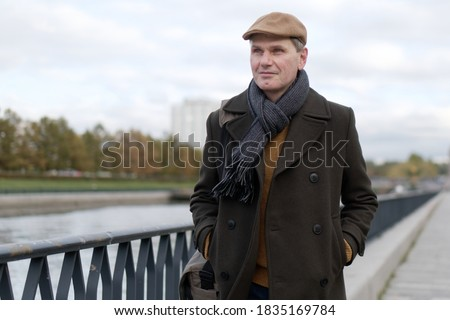 Fashionable mature man wearing woolen coat and Irish flat cap walking along canal quay  during overcast autumn day Royalty-Free Stock Photo #1835169784