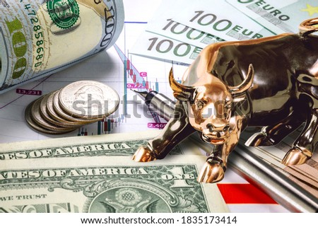 Concept of trading on the stock exchange market.  Copper bull standing near dollar and euro bills. Stock market prices chart in background. Stack of quarter cens and fountain pen in front.
