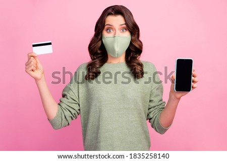 Astonished girl hold smartphone debit card recommend use bank online savings buyer service in covid quarantine wear green jumper medical isolated pastel color, background