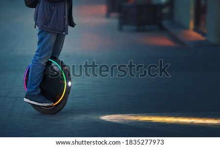 Riding fast on electric unicycle on city street at night with diode headlights. Night riding, man on electric mono-wheel riding fast (EUC). Mobile portable individual transportation vehicle.  #1835277973