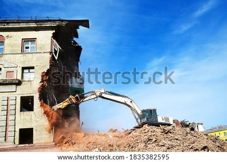 excavator demolishing a brick building. Machinery Demolishing Building #1835382595