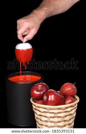 Conceptual image of a man dipping white apples into red paint to form edible red apples in a basket.
