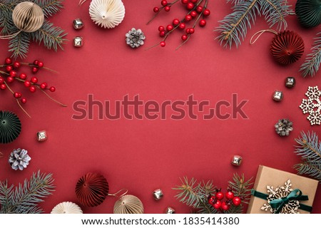 Christmas frame with gift box, paper decorations, spruce branches and berries on red background. Holiday border in earth colours. Royalty-Free Stock Photo #1835414380