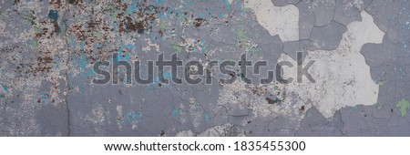 Peeling paint on the wall. Panorama of a concrete wall with old cracked flaking paint. Weathered rough painted surface with patterns of cracks and peeling. Wide panoramic grunge texture for background Royalty-Free Stock Photo #1835455300