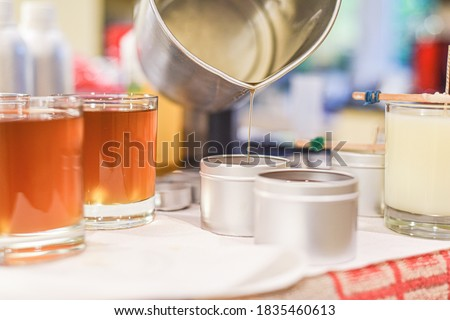 Creative occupation of candle making showing the pouring of liquid wax into jars Royalty-Free Stock Photo #1835460613